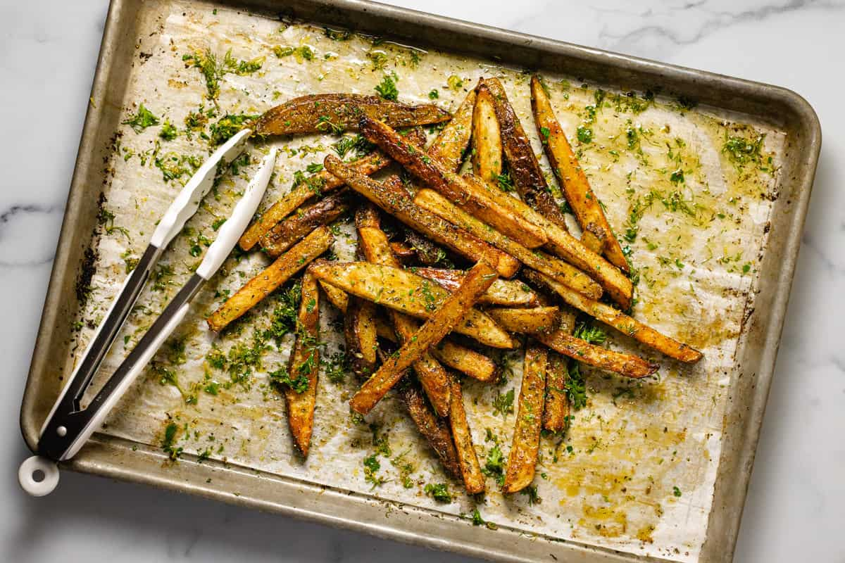 Baked fries being tossed together on a parchment lined baking sheet after baking