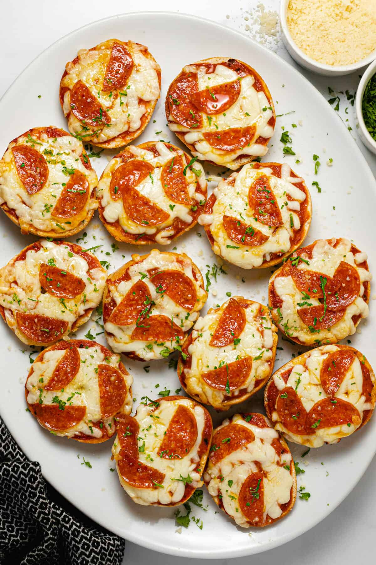 Large white platter filled with homemade pizza bagel bites garnished with parsley