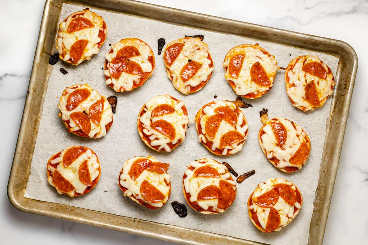 Freshly baked pizza bagel bites on a parchment lined baking sheet