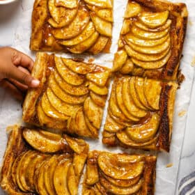 Overhead shot of a small hand reaching for slice of puff pastry apple tart