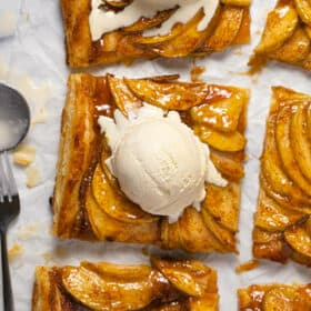 Overhead shot of a sliced puff pastry apple tart topped with ice cream