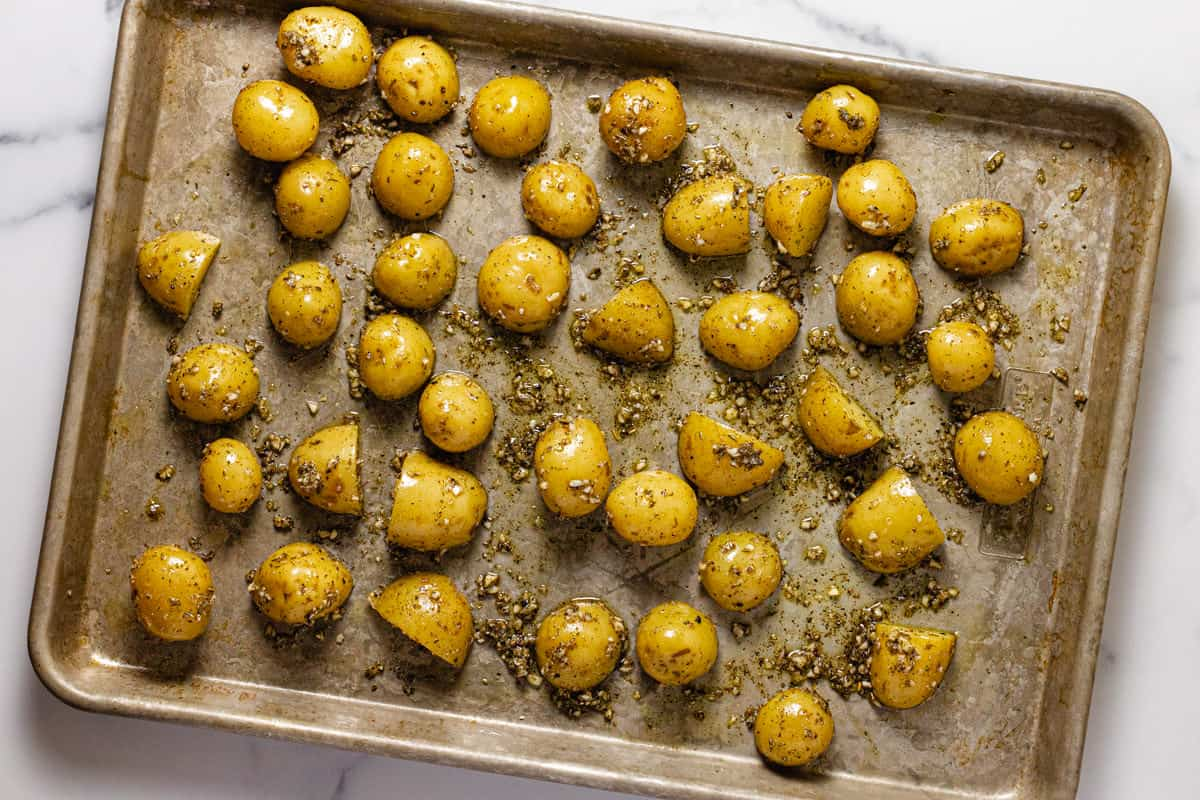 Baby potatoes tossed in olive oil herbs and garlic on a baking sheet