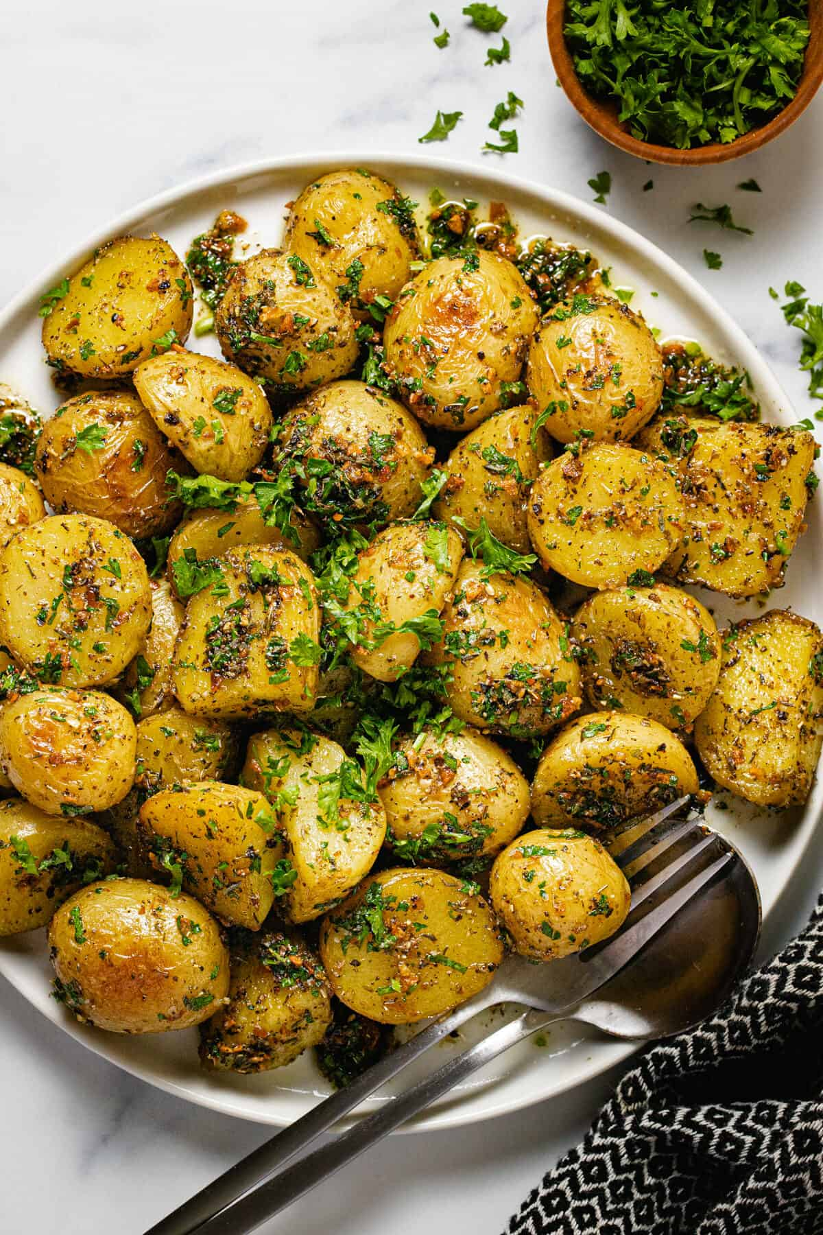 White plate filled with herby roasted baby potatoes garnished with parsley