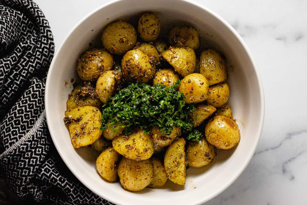 Roasted potatoes in a large white bowl with fresh chopped parsley