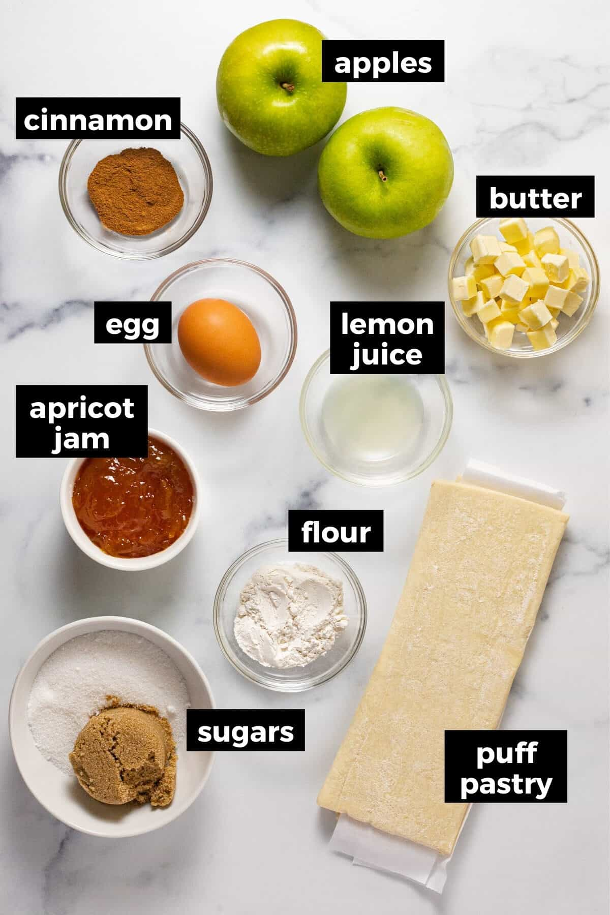 White marble counter top with ingredients to make apple pie with puff pastry
