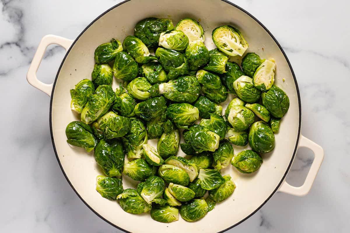 Large white pan filled with sautéed Brussel sprouts