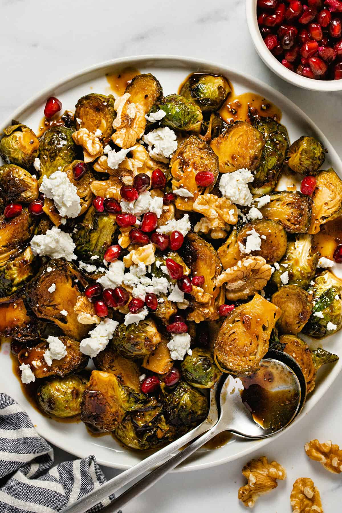 Overhead shot of balsamic glazed Brussel sprouts topped with goat cheese pomegranate seeds and walnuts