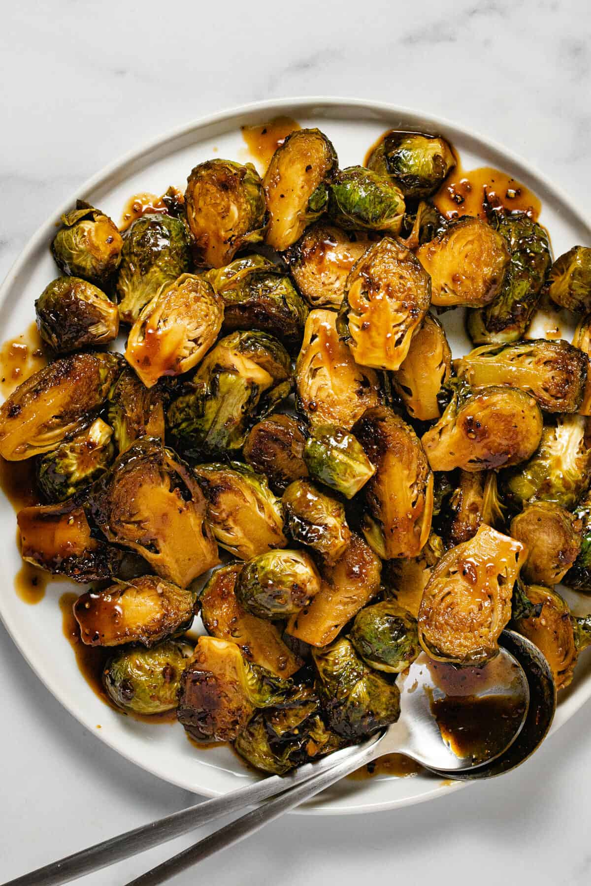 Overhead shot of balsamic glazed Brussel sprouts on a white plate