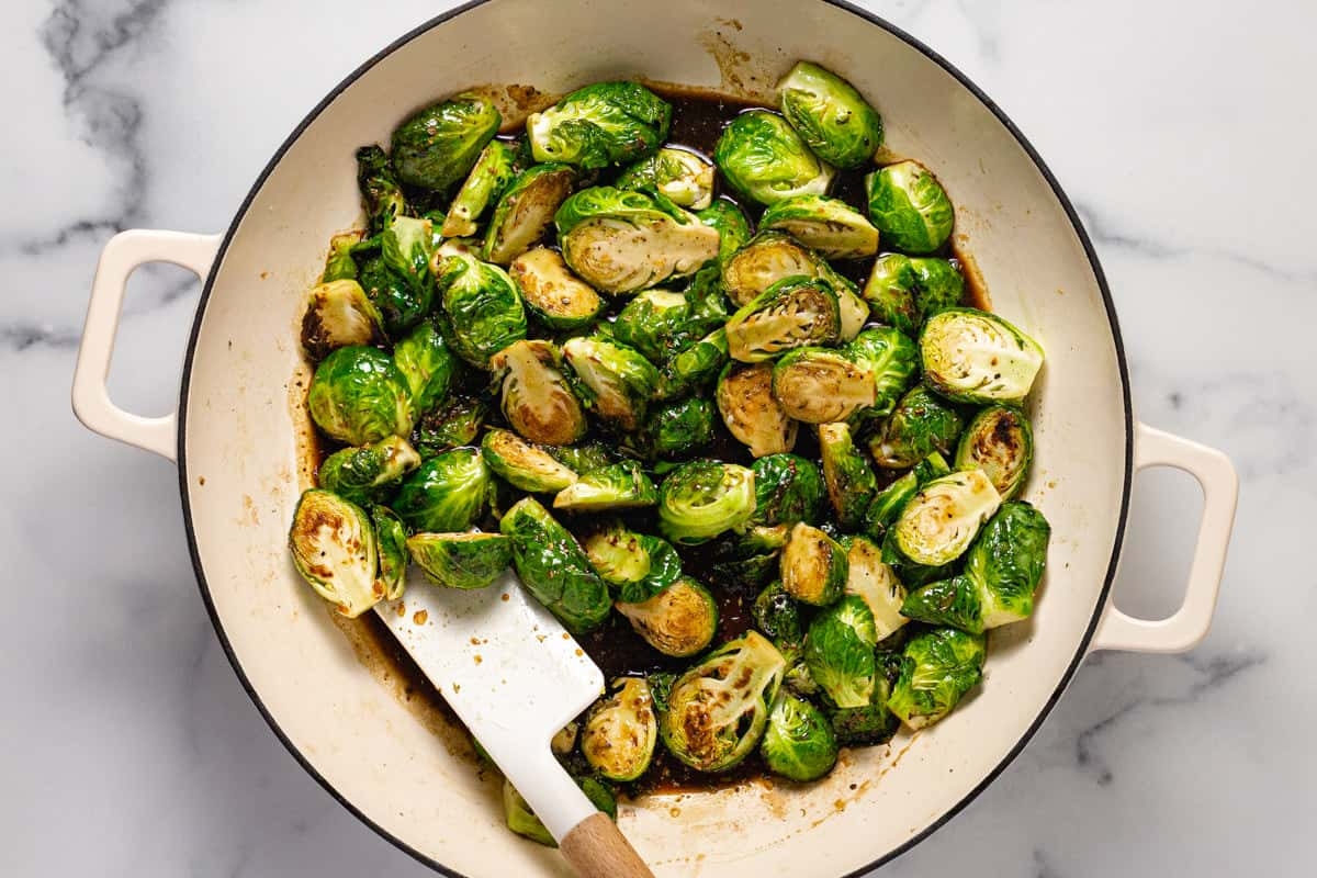 Balsamic glazed Brussel sprouts cooking in a large white pan