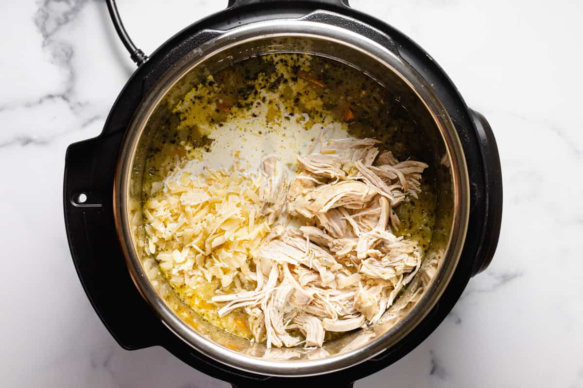 Instant pot filled with ingredients to make chicken and rice soup