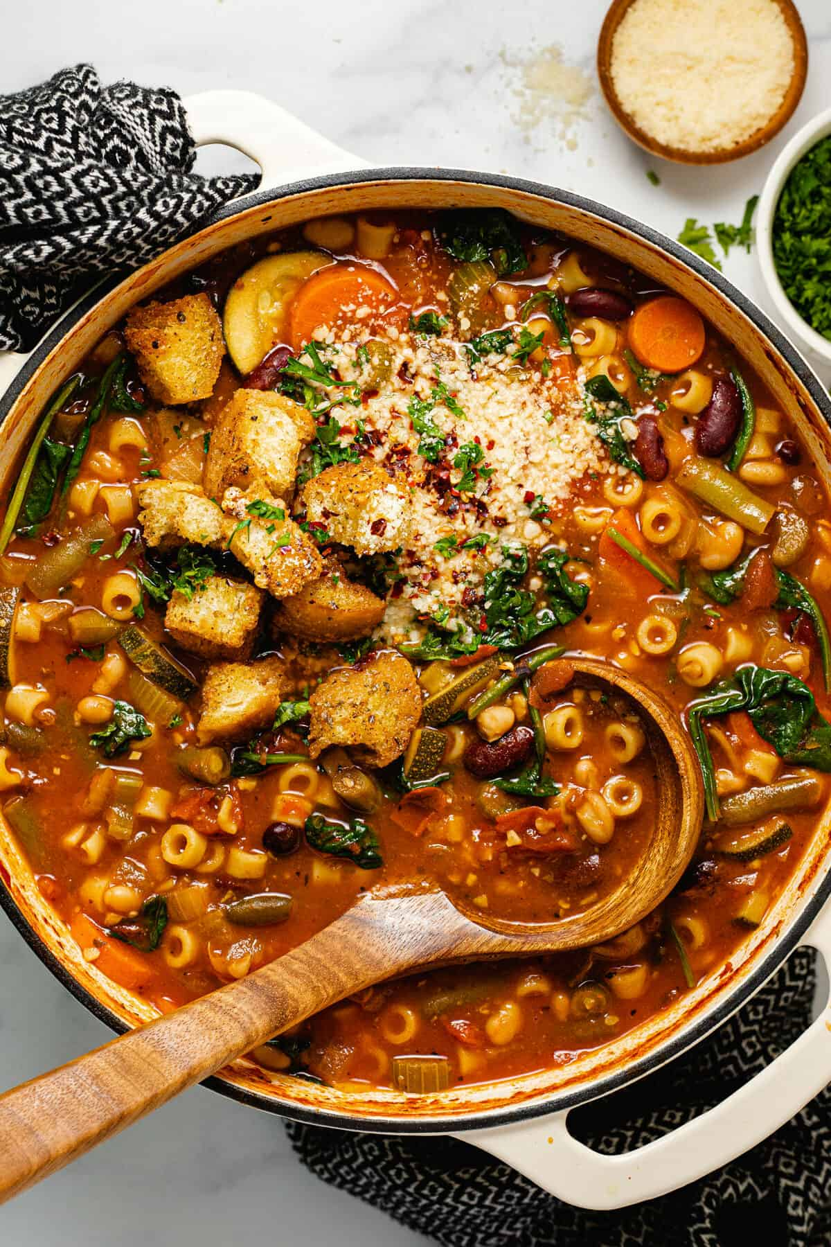Overhead shot of a pot of minestrone soup garnished with croutons and Parmesan