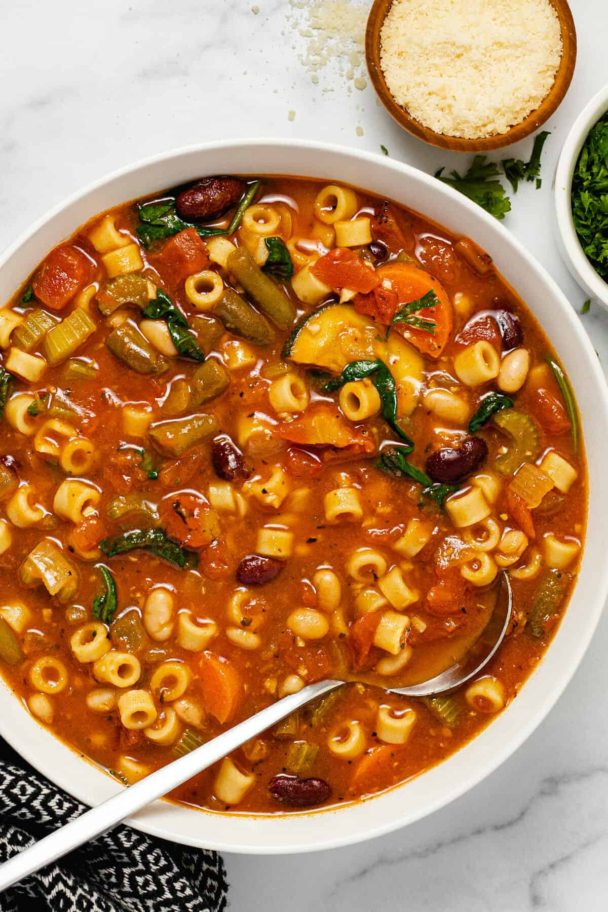 Overhead shot of a white bowl filled with vegan minestrone soup