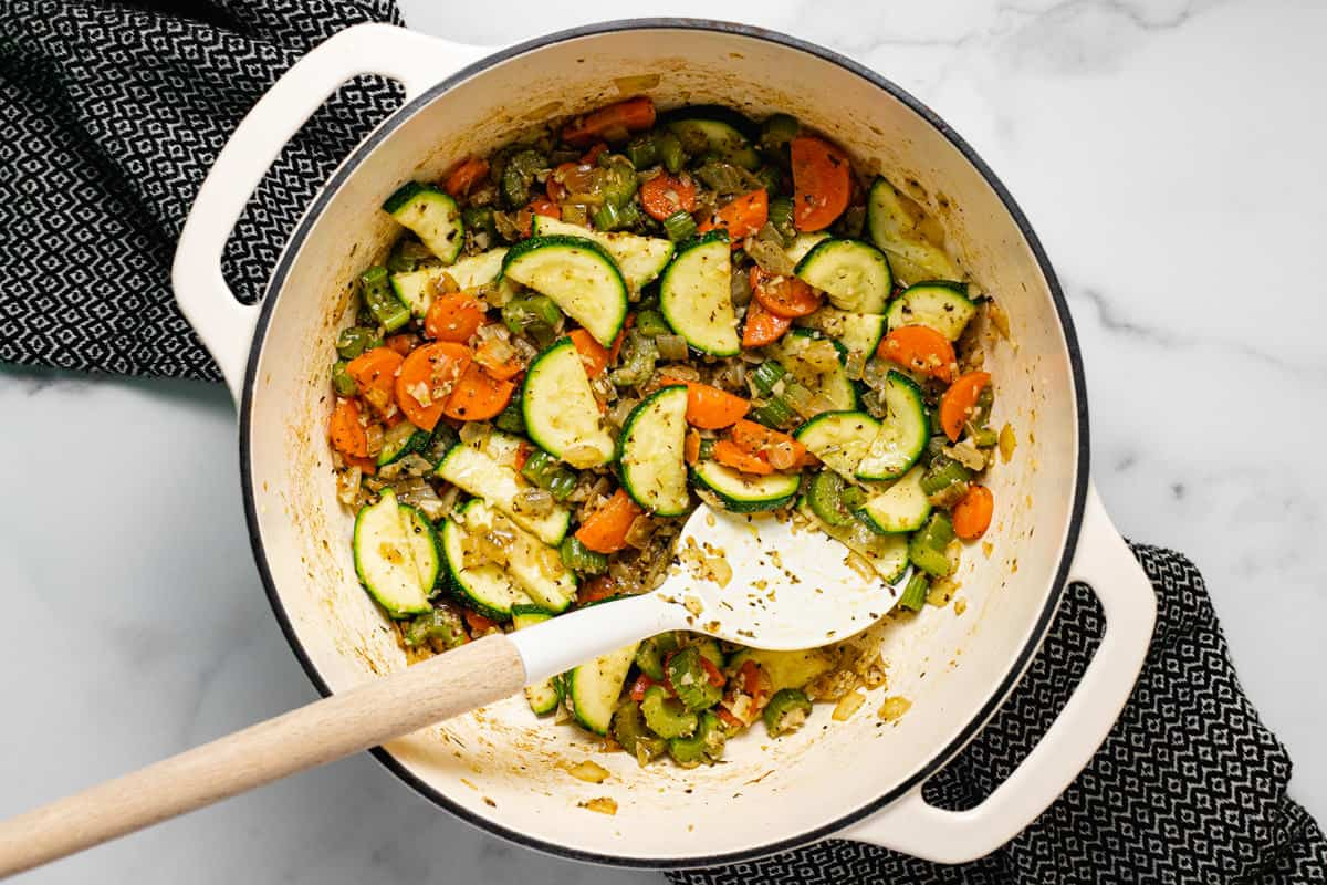 Large white pot filled with sautéed veggies