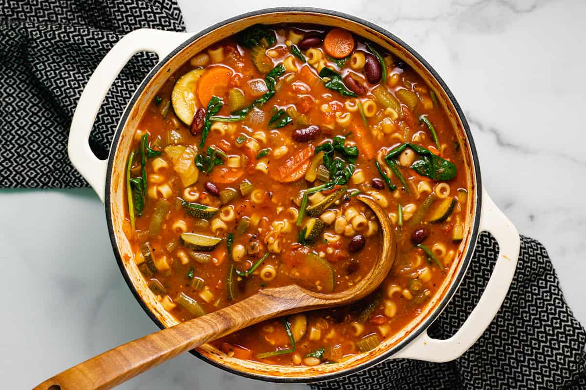 Large white pot filled with ingredients to make minestrone soup